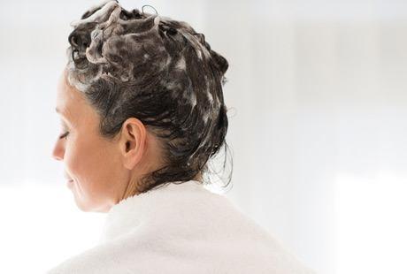 Kvinne med håret fullt av shampoo. Hun har mørkt hår og et hvitt håndkle rundt skuldrene.