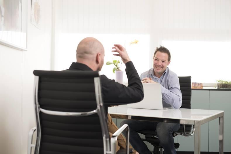 En skallet mann i sort genser med ryggen til og en mannlig hårkonsulent i lys skjorte sittende ved et skrivebord.