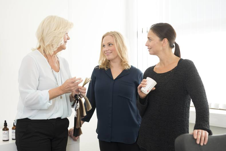 Hårtap hos kvinne. Kvinnelig hårspesialist forklarer to kvinner hvilke løsninger Apollo har for hårtap. To kvinner har blondt, en har mørkt hår.