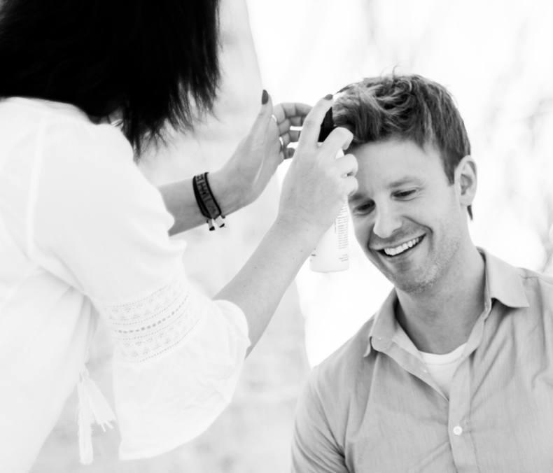 Kvinnelig frisør steller håret til mannlig kunde