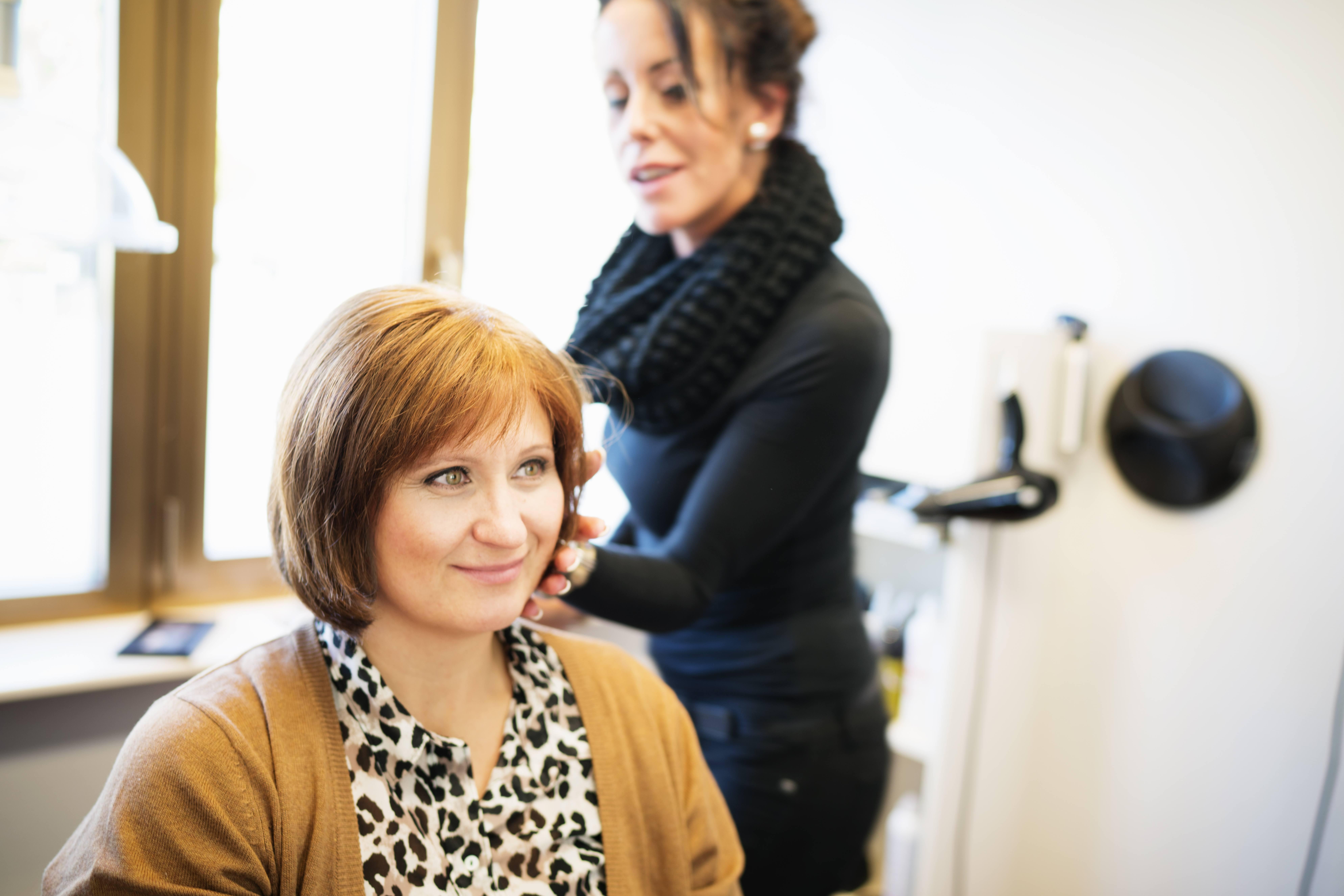 Anita har på seg en mønstret bluse og cardigan. Hun sitter i en frisørstol og smiler mens håret hennes blir stelt av en spesialist.