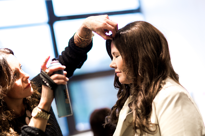 Frisøren styler og sprayer det flotte lange håret til Monica.