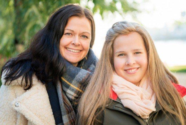 Andrea og moren smiler mot kamera. Begge to har langt og vakkert hår.