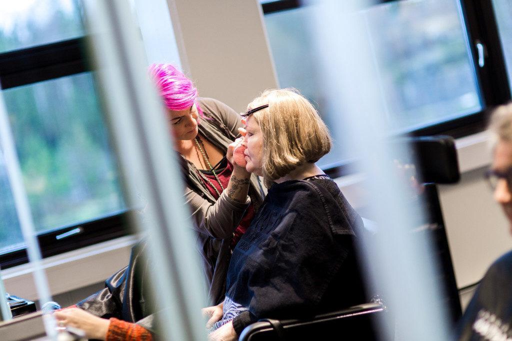 Laila sitter i en frisørstol og blir stelt av en hårspesialist