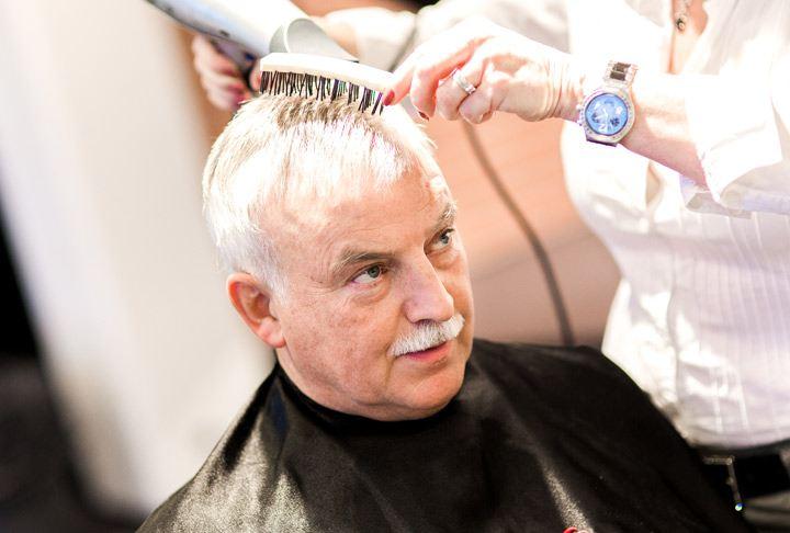 Arnvid sitter i frisørstolen og får stelt håret sitt. Han bruker hårdel som er festet i hans eget hår.