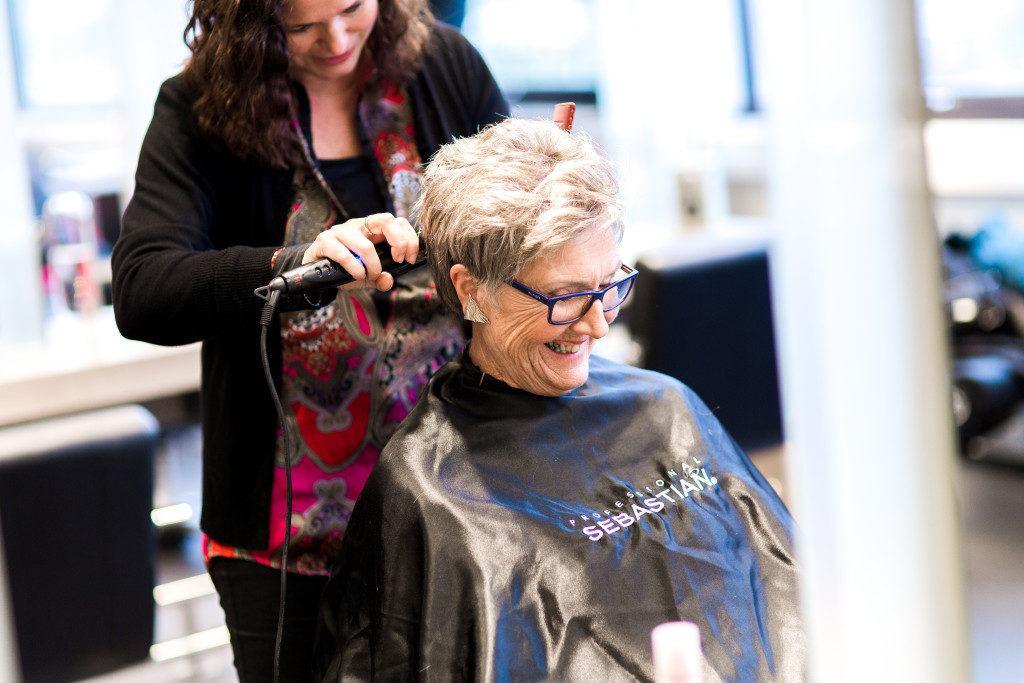 Hellen sittter smilende i salongen mens spesialisten ordner frisyren hennes.
