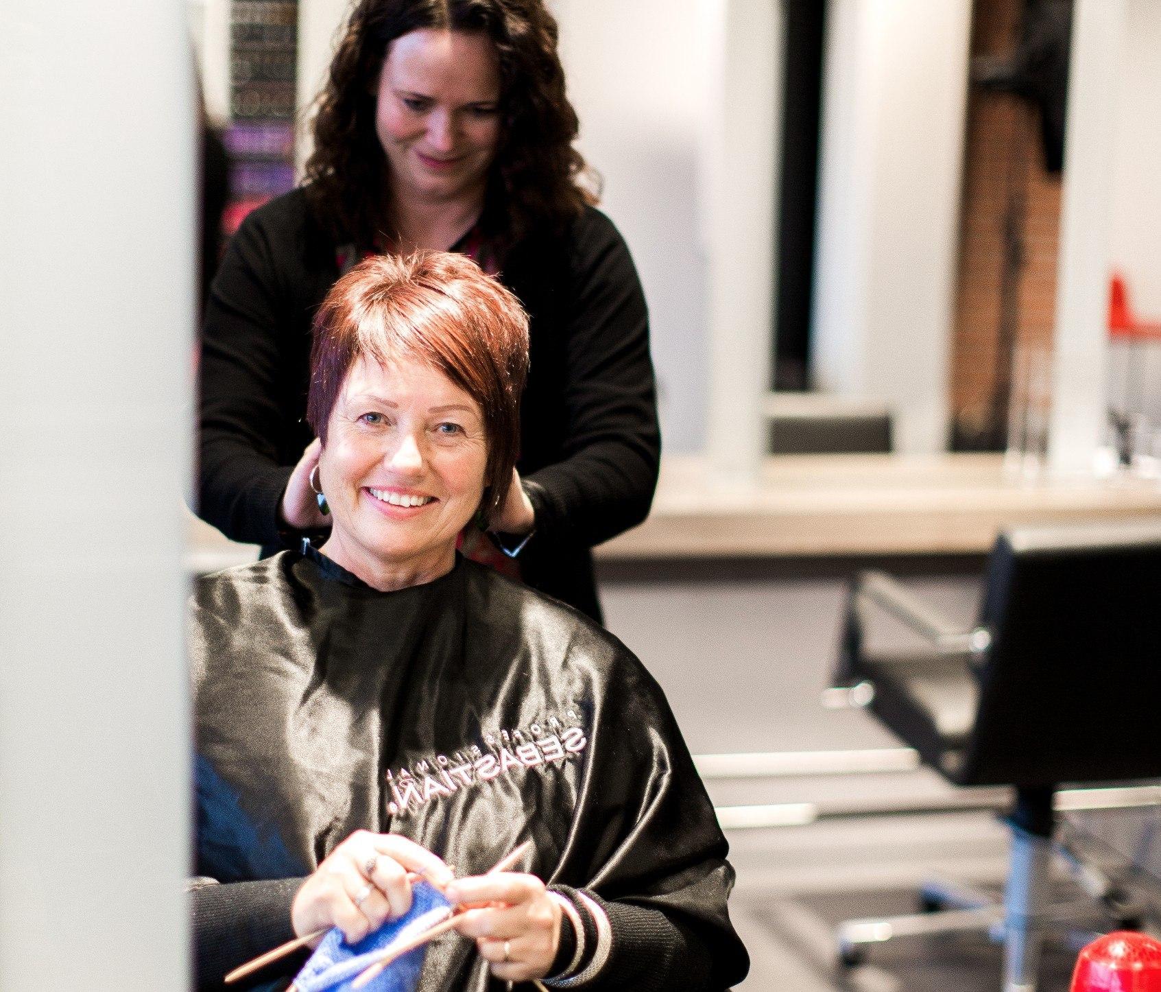 Marit sitter i en frisørstol og strikker. Hårspesialisten fikser håret hennes.