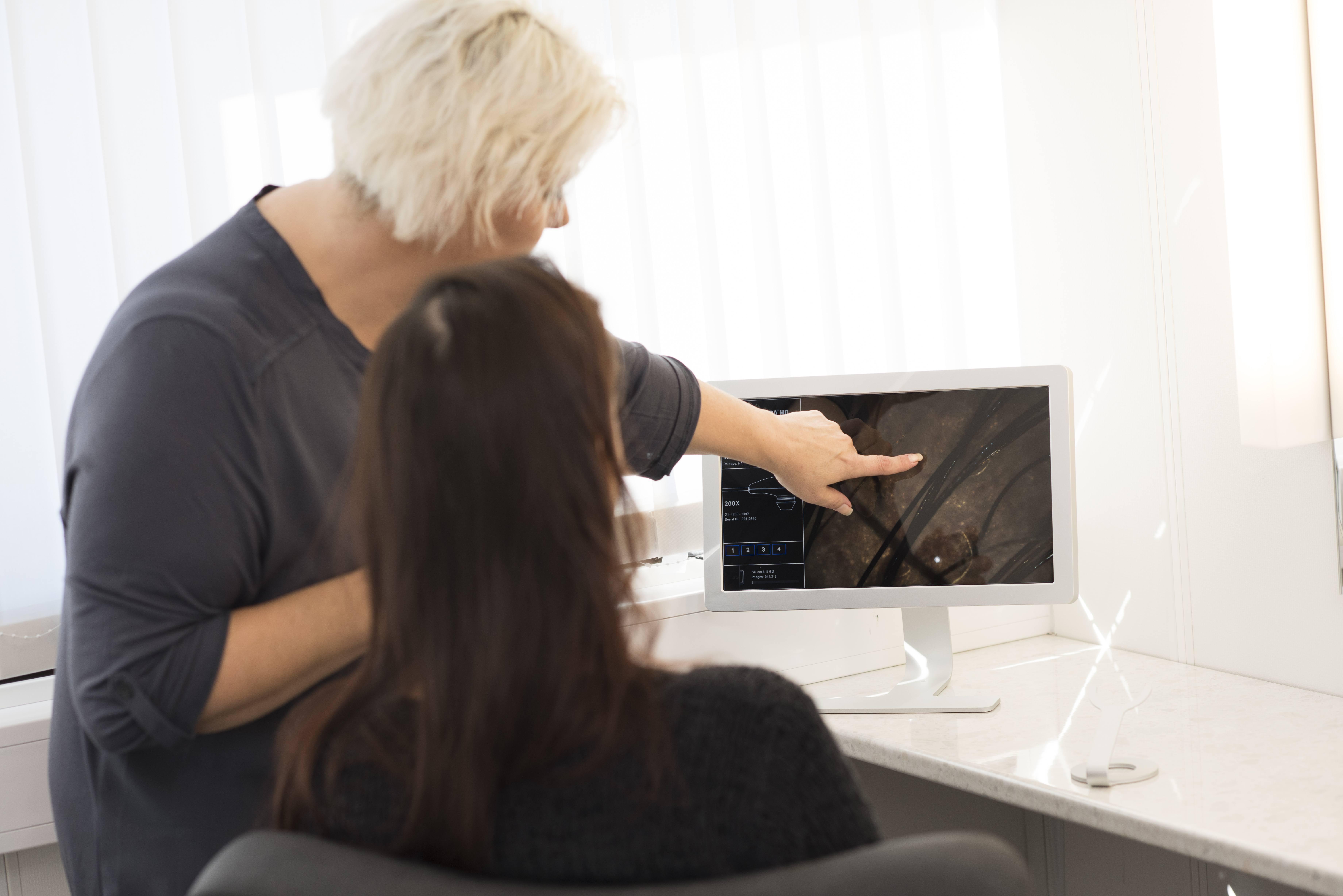 En mørkhåret kvinne sitter med ryggen til og en annen kvinne med lyst hår står ved siden av og peker på en skjerm.