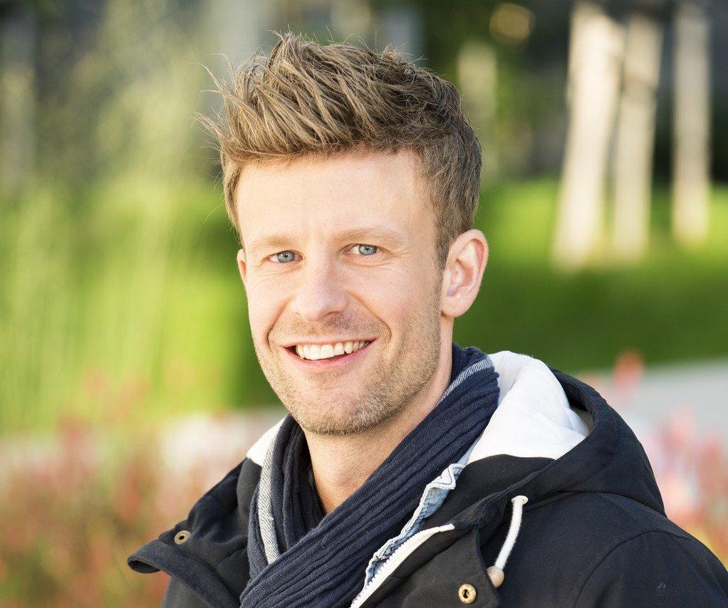 Ung mannlig hårmodell med blondt hår utendørs