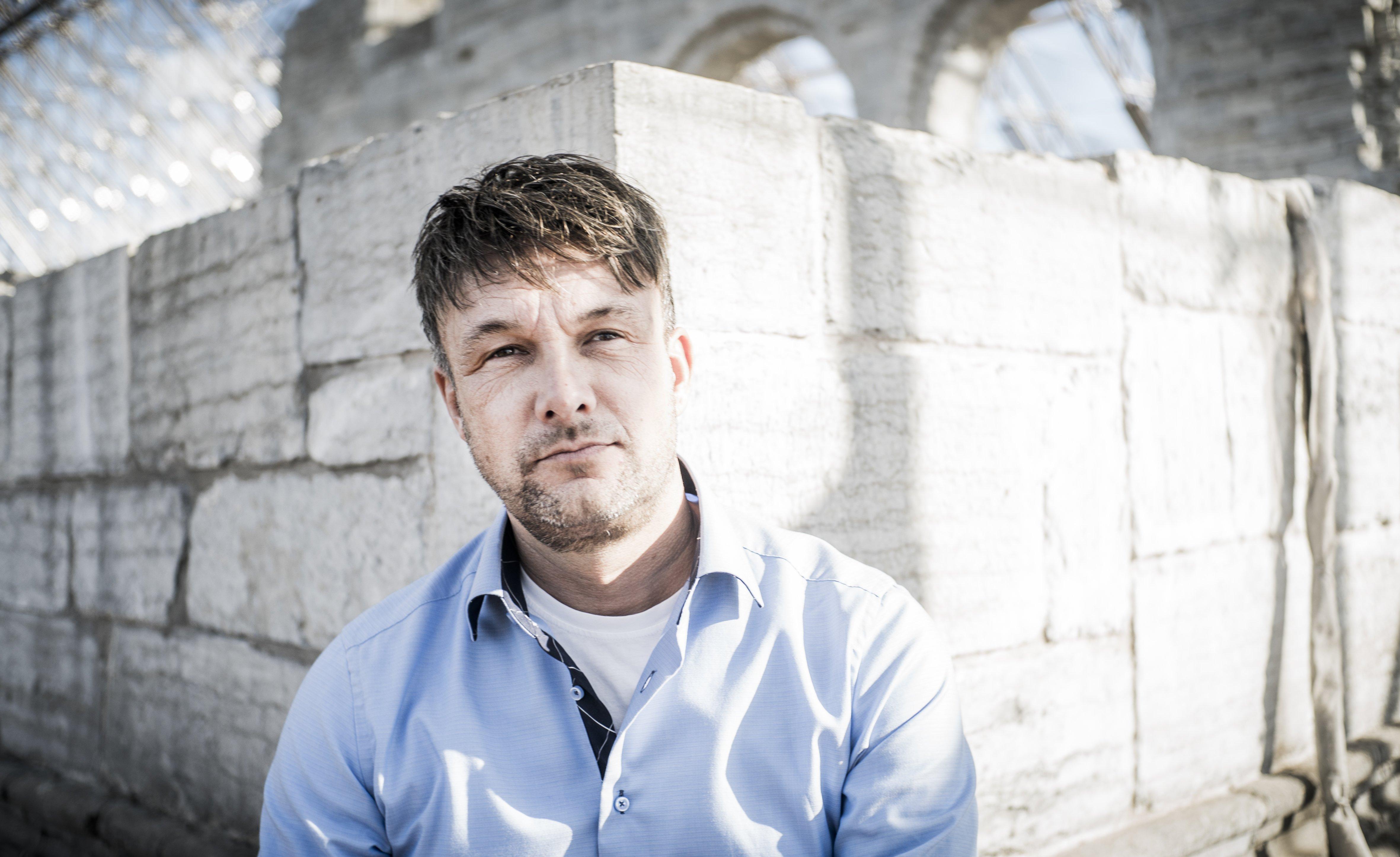 Mann i blå skjorte utendørs foran gamle ruiner i