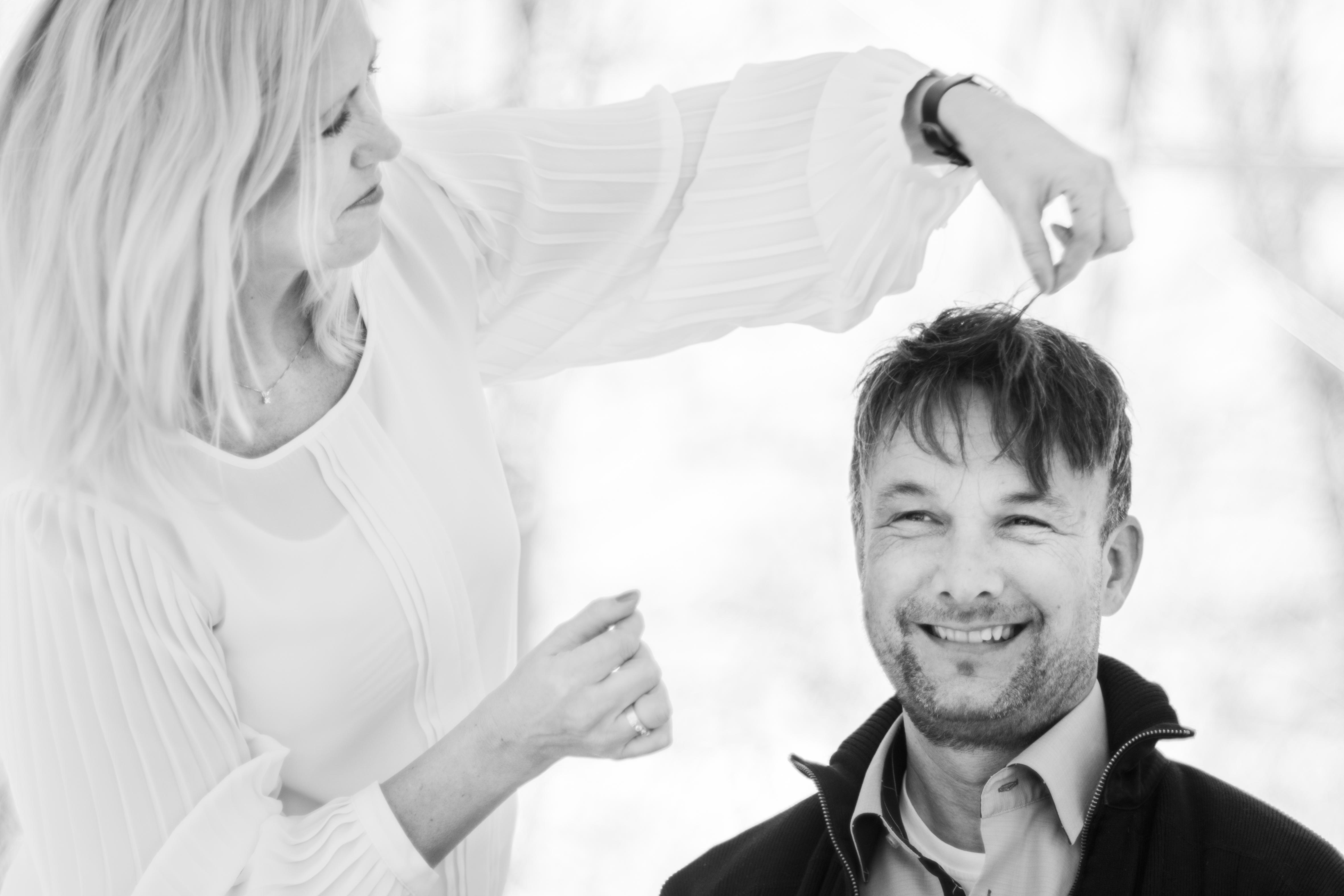 Mann som smiler og blir stelt på håret