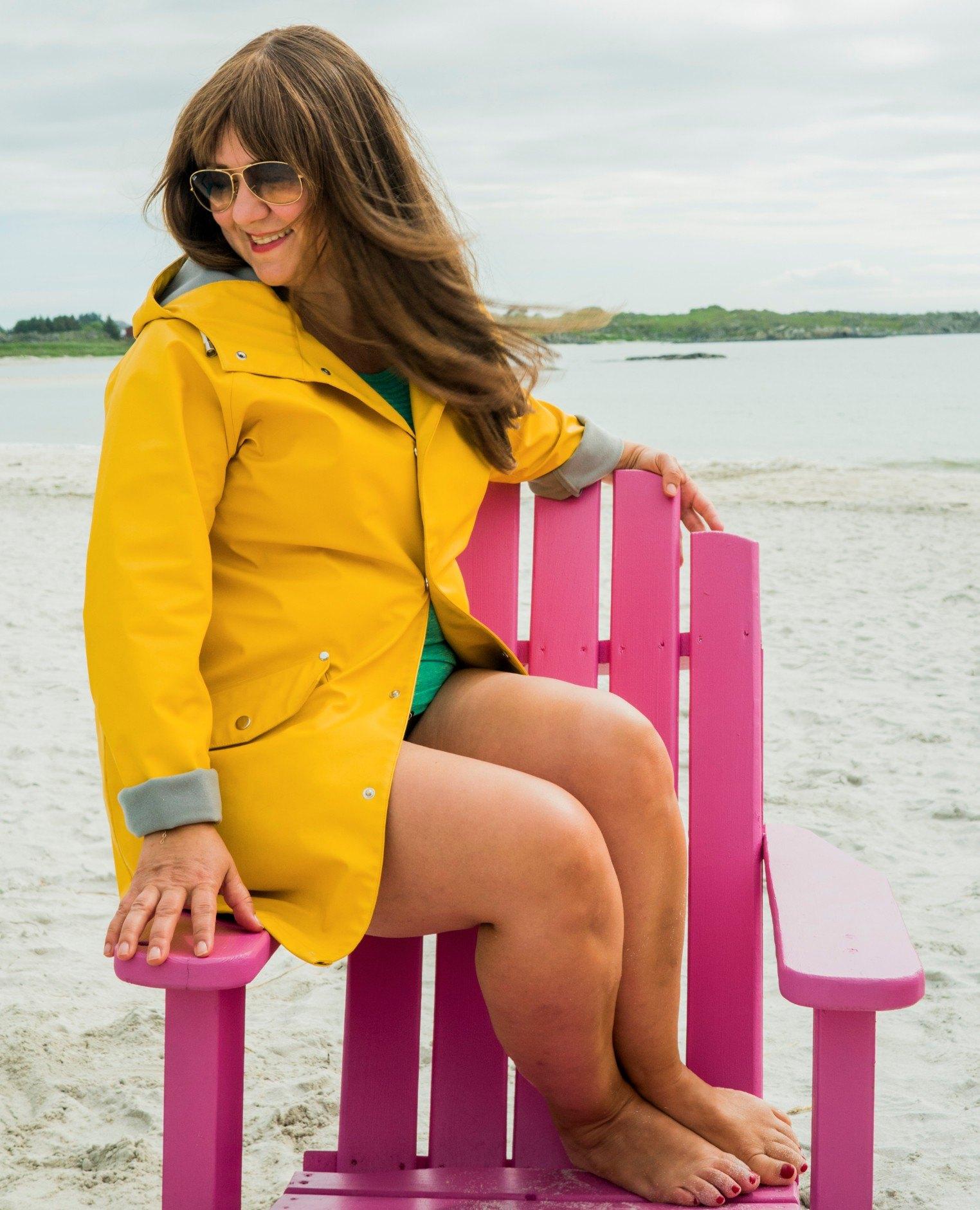 Silje sitter i badedrakt og gul regnjakke på en rosa stol. Hun har solbriller på og håret flommer ut over skulderene.