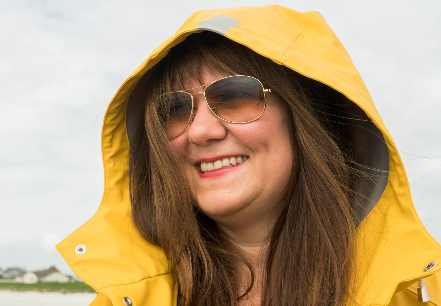 Silje smiler med gul regnjakke. Langt hår flommer ut fra under hetten.