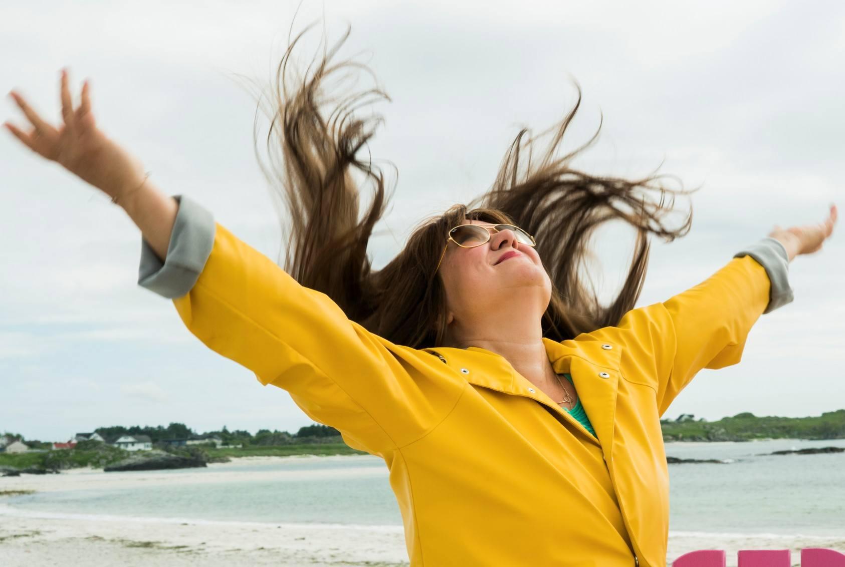 Silje er kledd i gul regnjakke og danser på stranden. Håret flagrer i vinden.