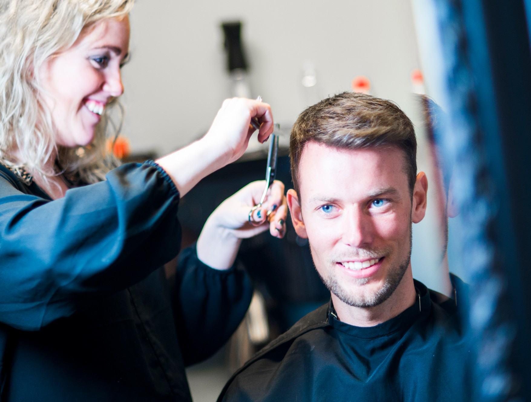 Glenn sitter i frisørstol og smiler. Det står en smilende frisør og klipper han.