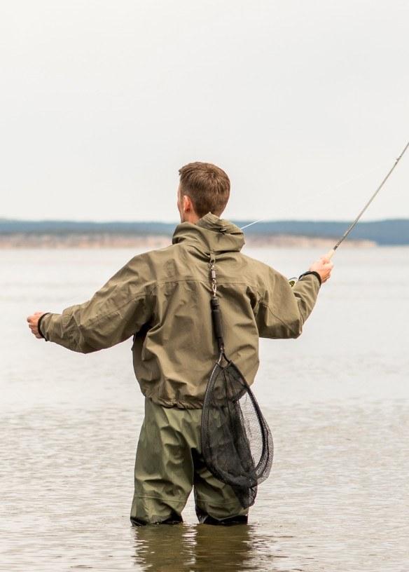 Glenn står med vann til knærne i en innsjø. Han har fiskestang og utstyr, og er klar for et kast.
