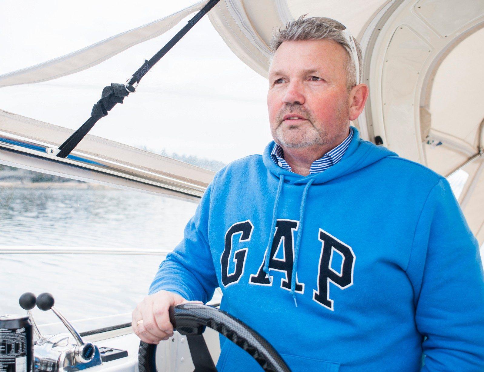 Tom står bak rattet på båten sin og skuer utover havet.