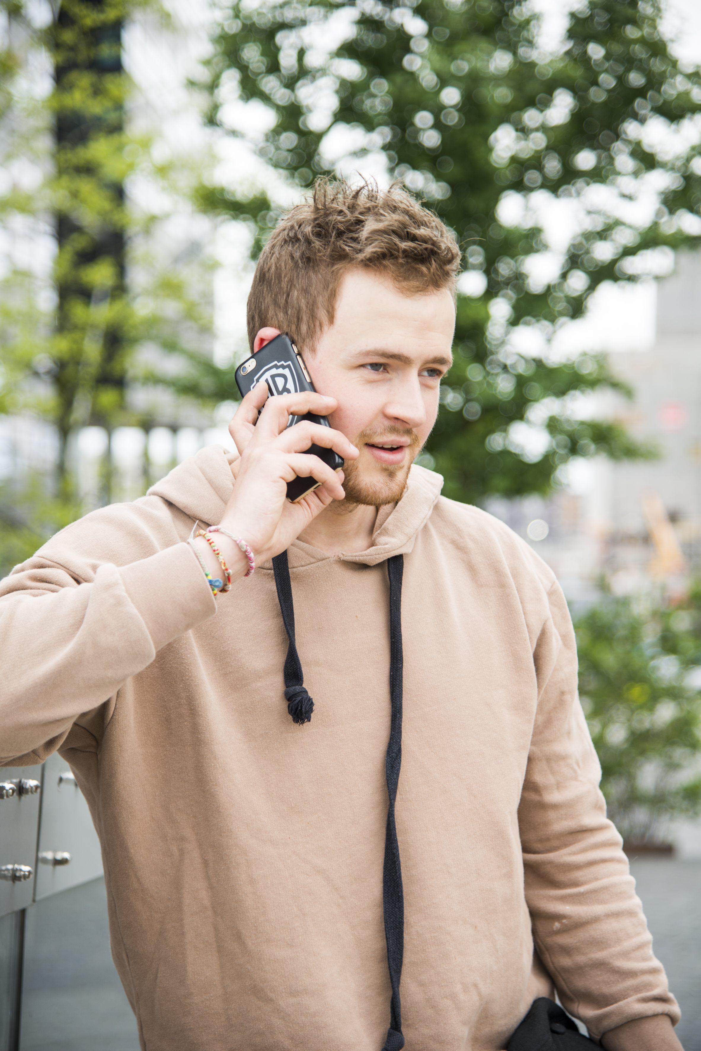 Julian sett fra siden mens han snakker i mobil og lener seg mot gjerde. Hårdelen ser helt naturlig rufsete ut.