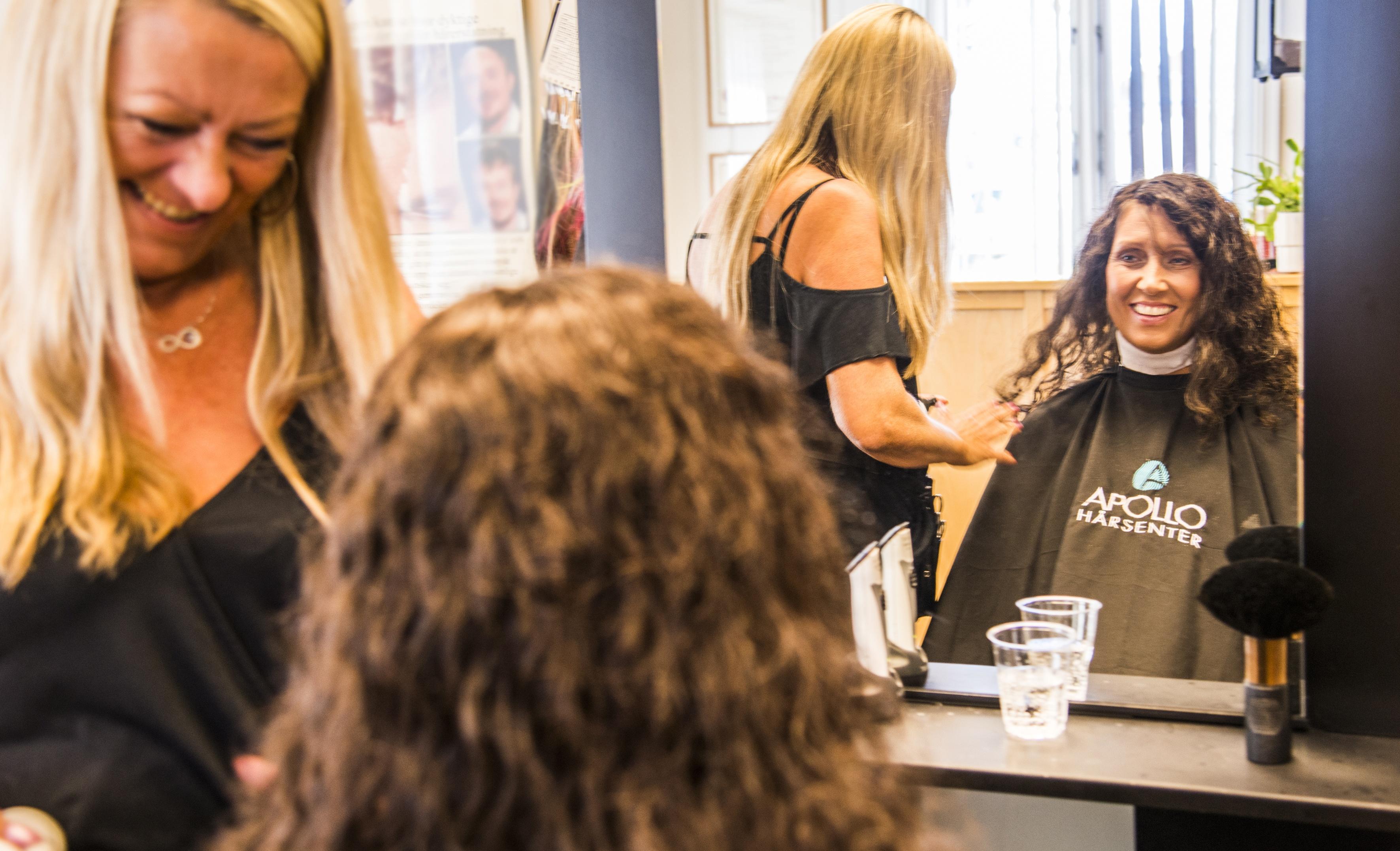 Cathrine sitter i salongen til Apollo Hårsenter Sandefjord. Hun ser seg i speilet og smiler.