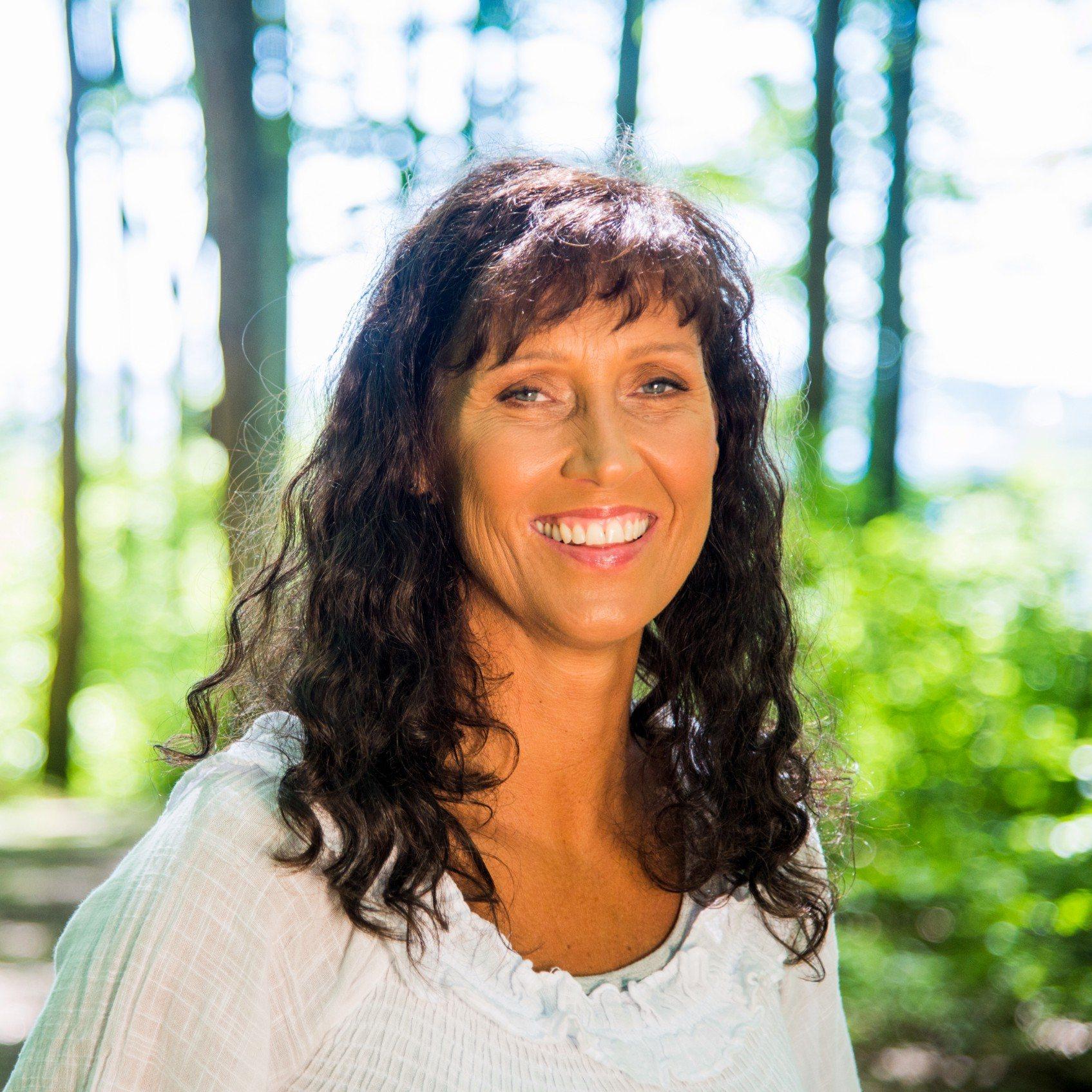 Cathrine fotografert i bjørkeskogen. Hun smiler bredt og det bølgete håret ligger fint over skuldrene.
