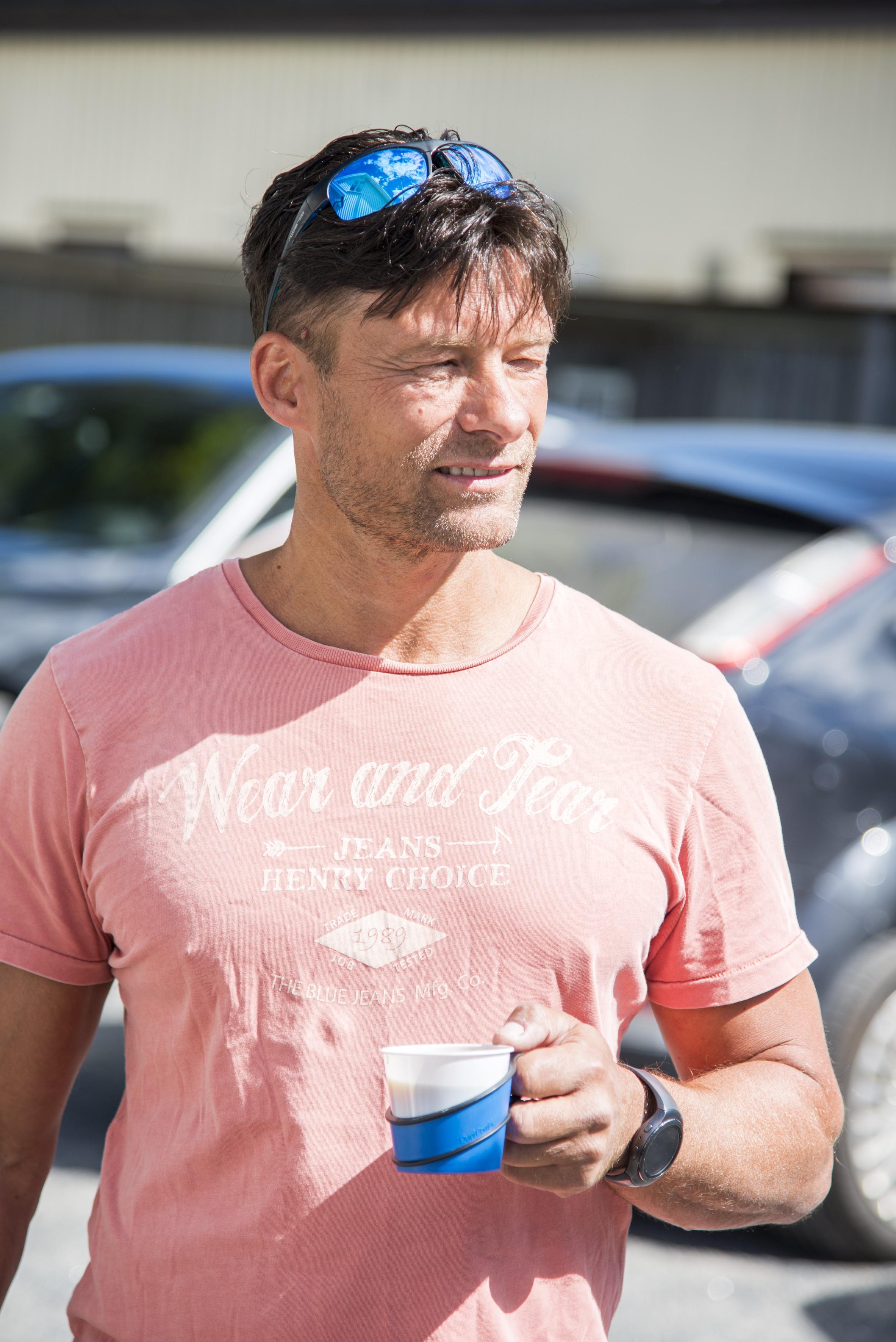 Frank avbildet med tskjorte og solbriller. Han holder en kaffekopp i hånden.