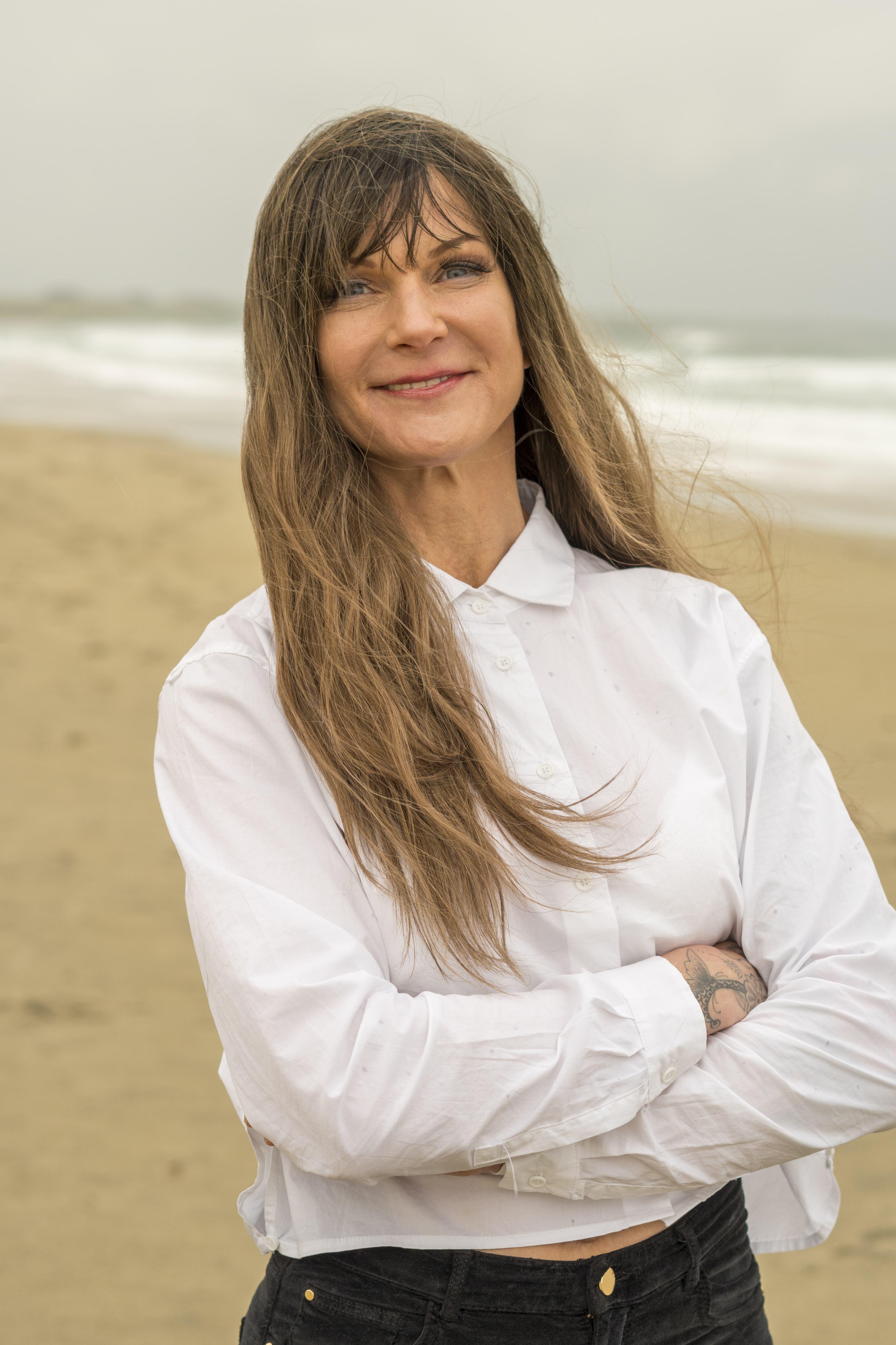 Helen står på stranden med sitt lange hår utslått.
