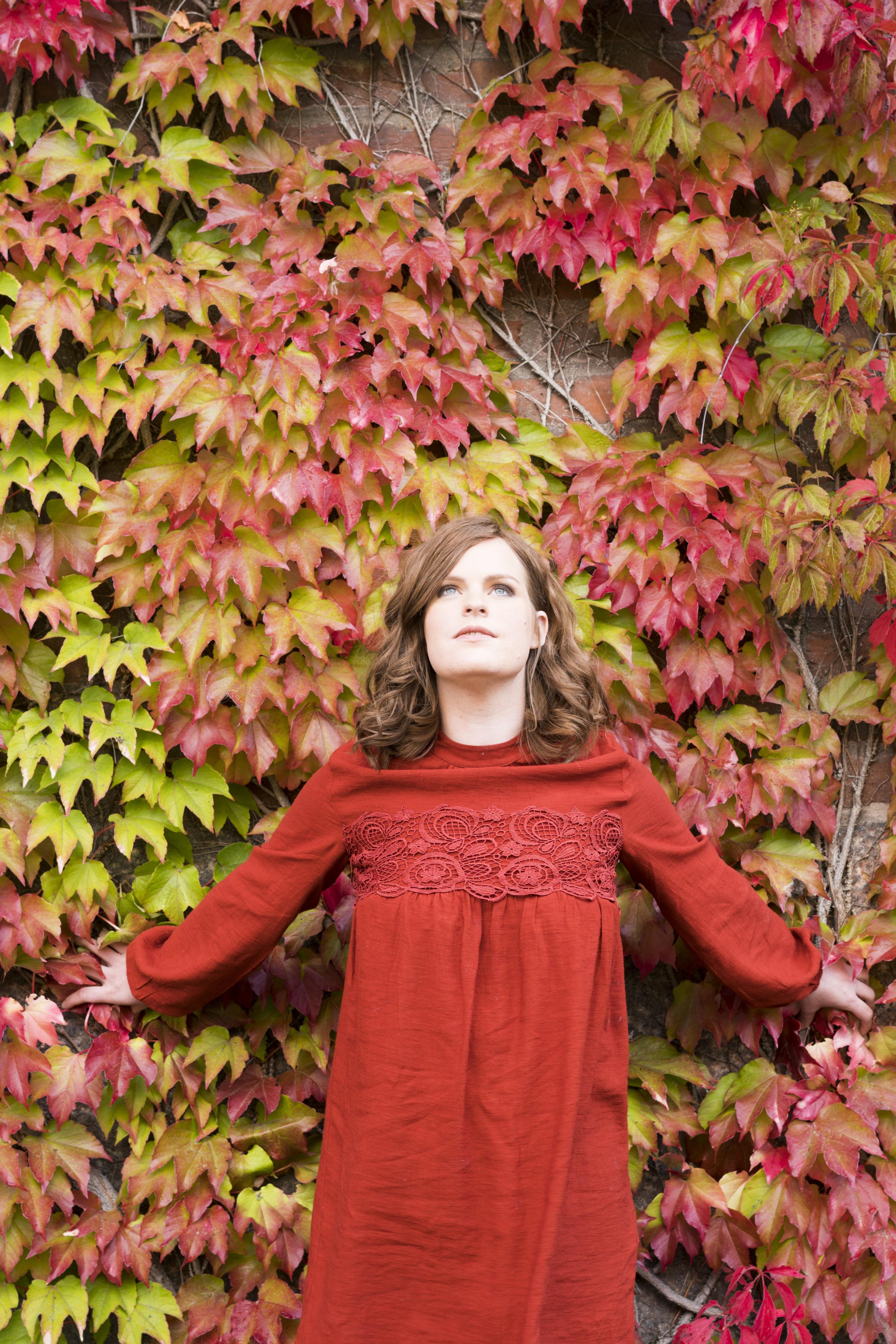 Erika er avbildet i rød kjole foran en vegg fylt med grønne og røde blader.
