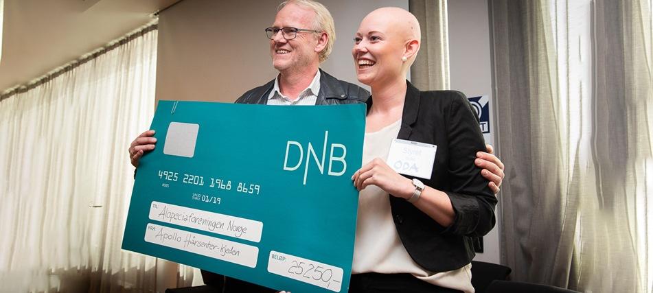 Apollo Hårsenters Olav Midtgarden deler ut sjekk til Alopeciaforeningen