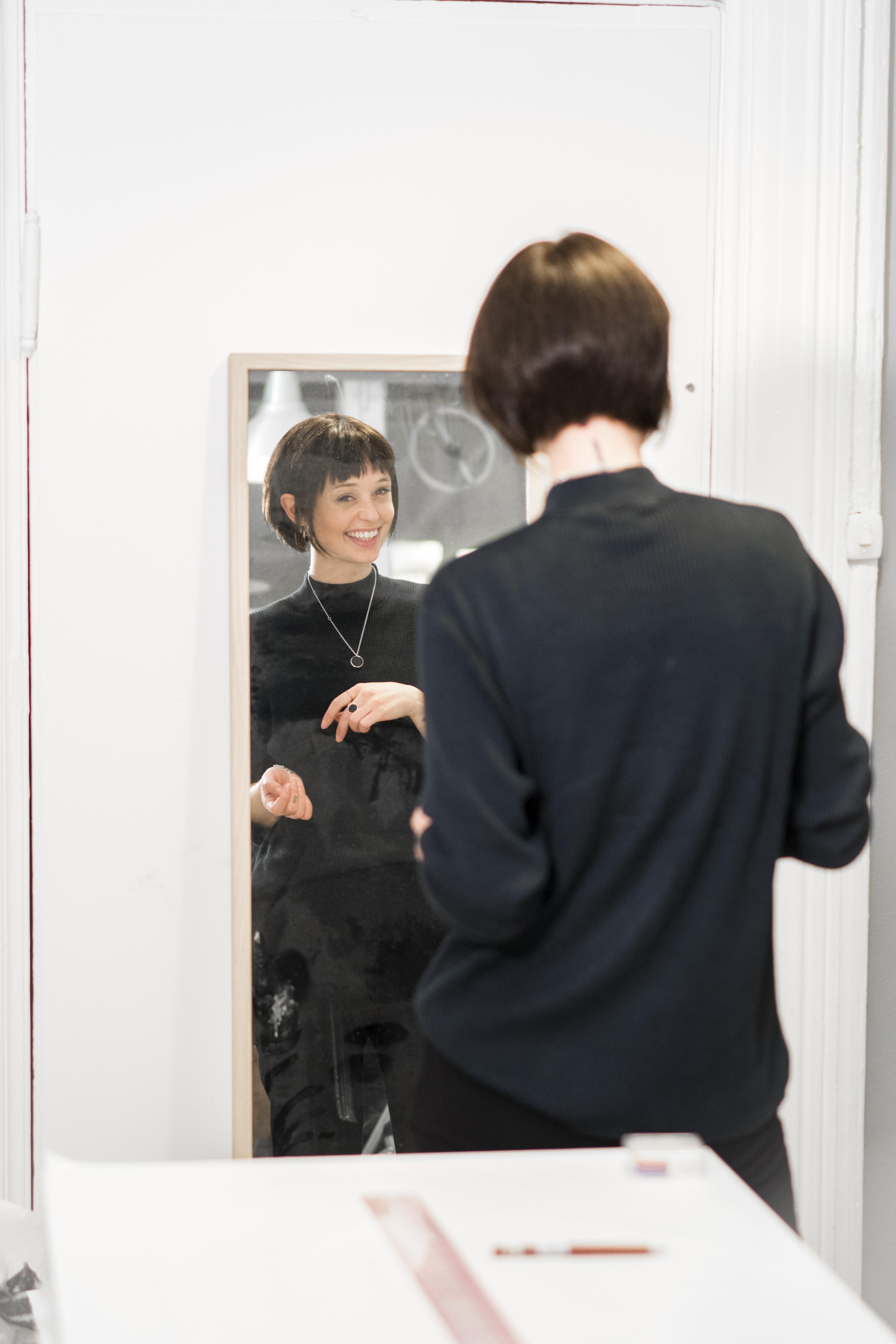 ung kvinne med hårdel som ser seg i speilet