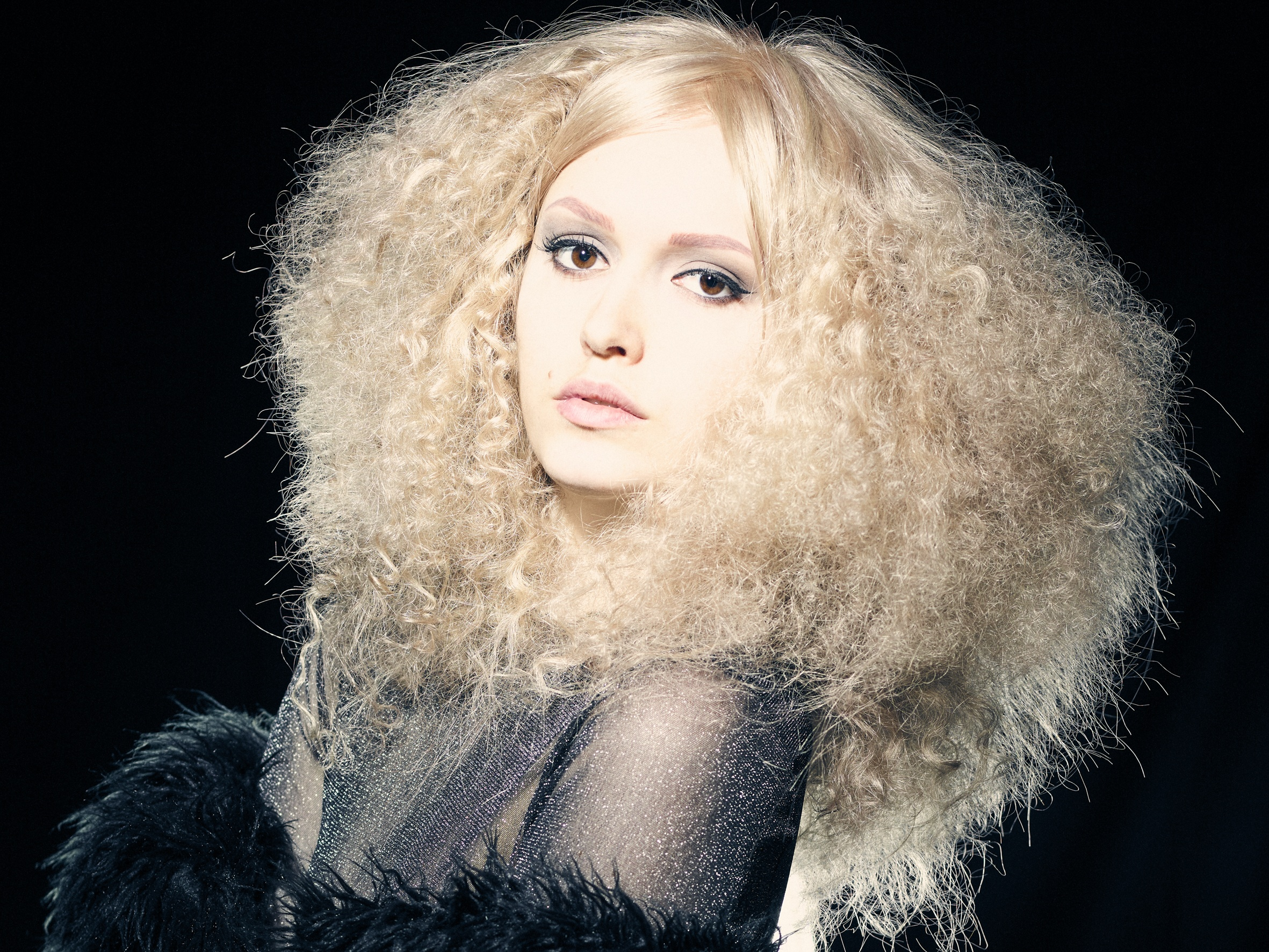 Sofia hårmodell med alopecia har på lys krøllete parykk