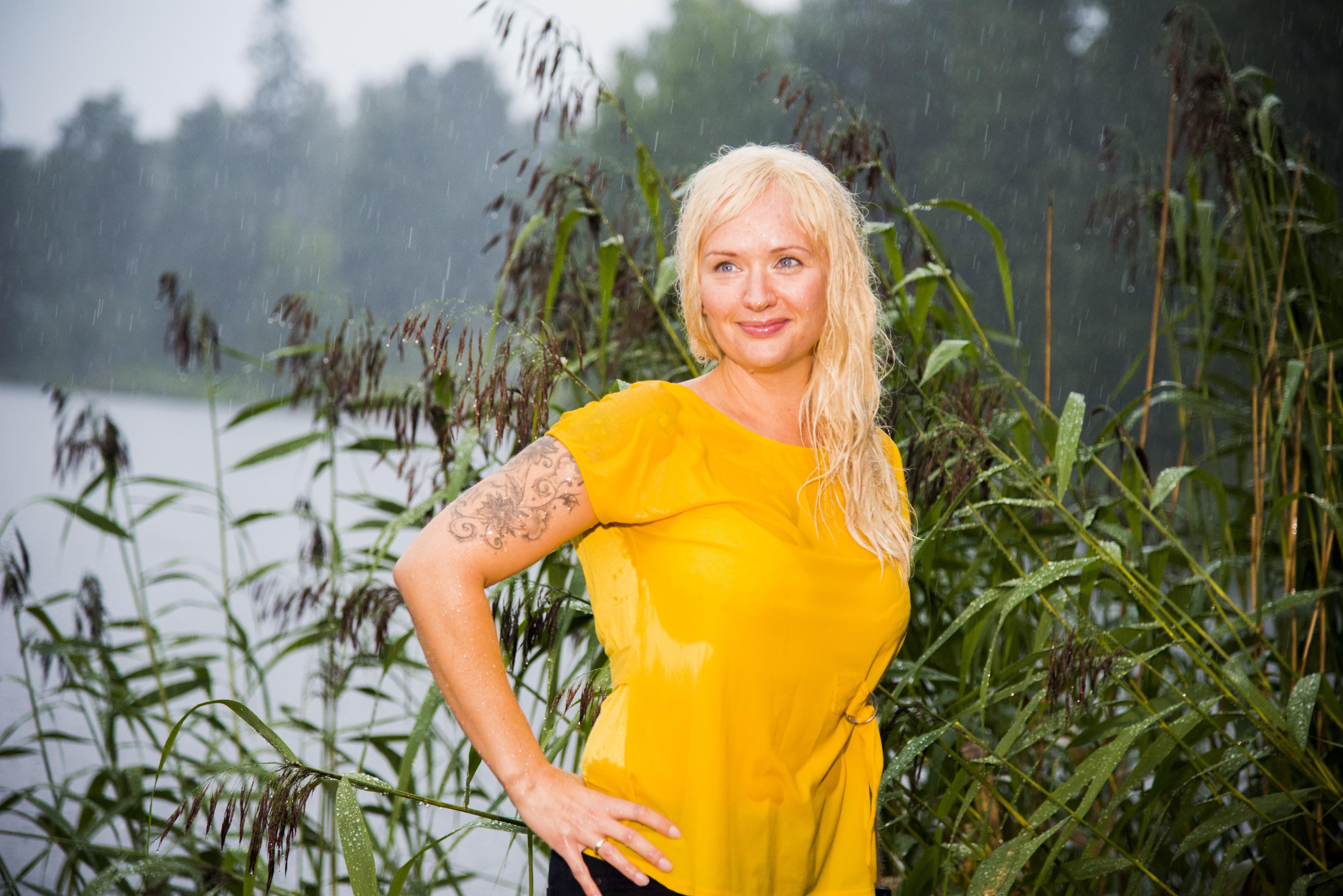 Kvinne i gul topp med lyst hår. Står ute i regnet og er våt. Bruker hårdel