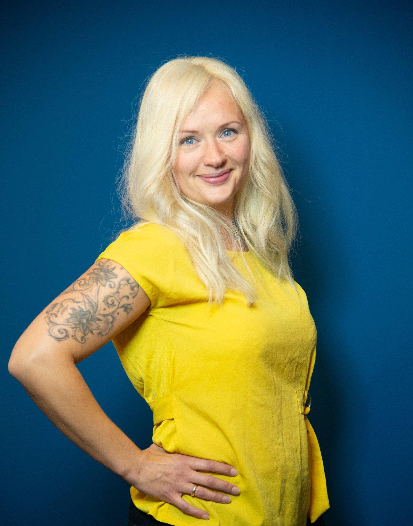 Kvinne i gul topp med lyst hår som bruker hårdel