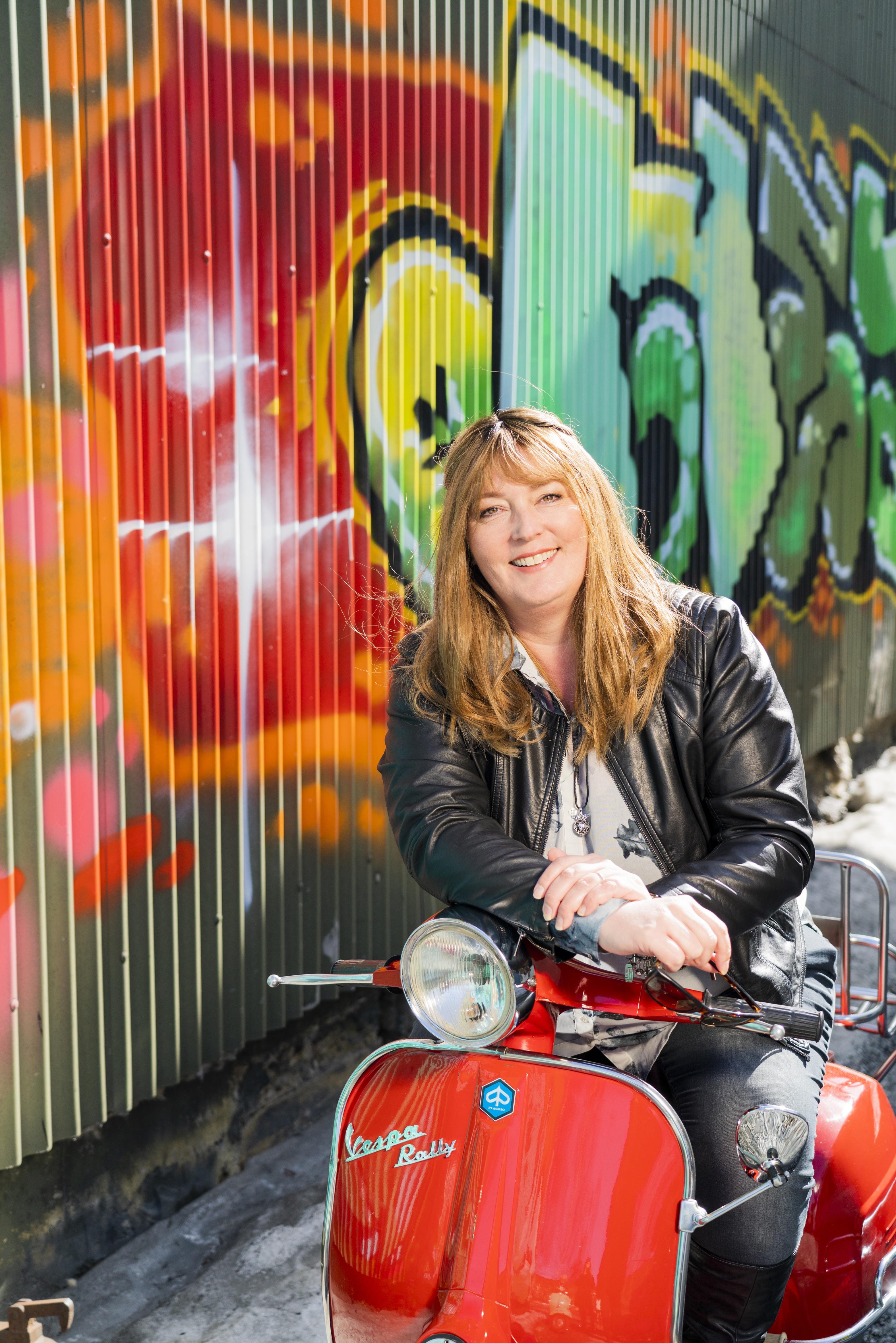 kvinne med flott hår som sitter på rød scooter