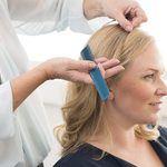 Kvinne i profil med lyst hår blir stelt av frisør med kam
