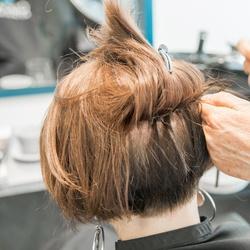 En kvinne med kort, mørkt hår får påsatt hårdeler