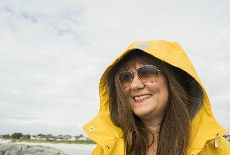 Silje har på seg solbriller og gul regnjakke. Hennes lange flotte hår blåser i vinden og hun smiler bredt.