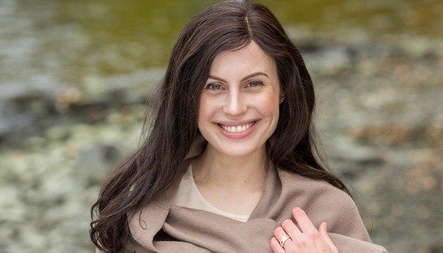 Ung, vakker kvinne som smiler med langt mørkt hår. Kvinnen har Alopecia og bruker parykk for å løse sitt hårtap.