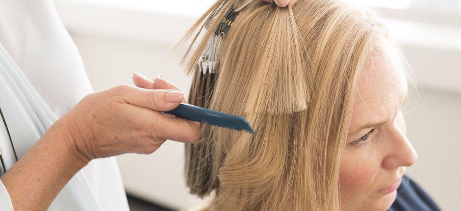 Hårspesialisten løfter opp hår fra hodet til kvinnen og ser på det.